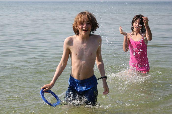 Siblings playing frisbee in lake