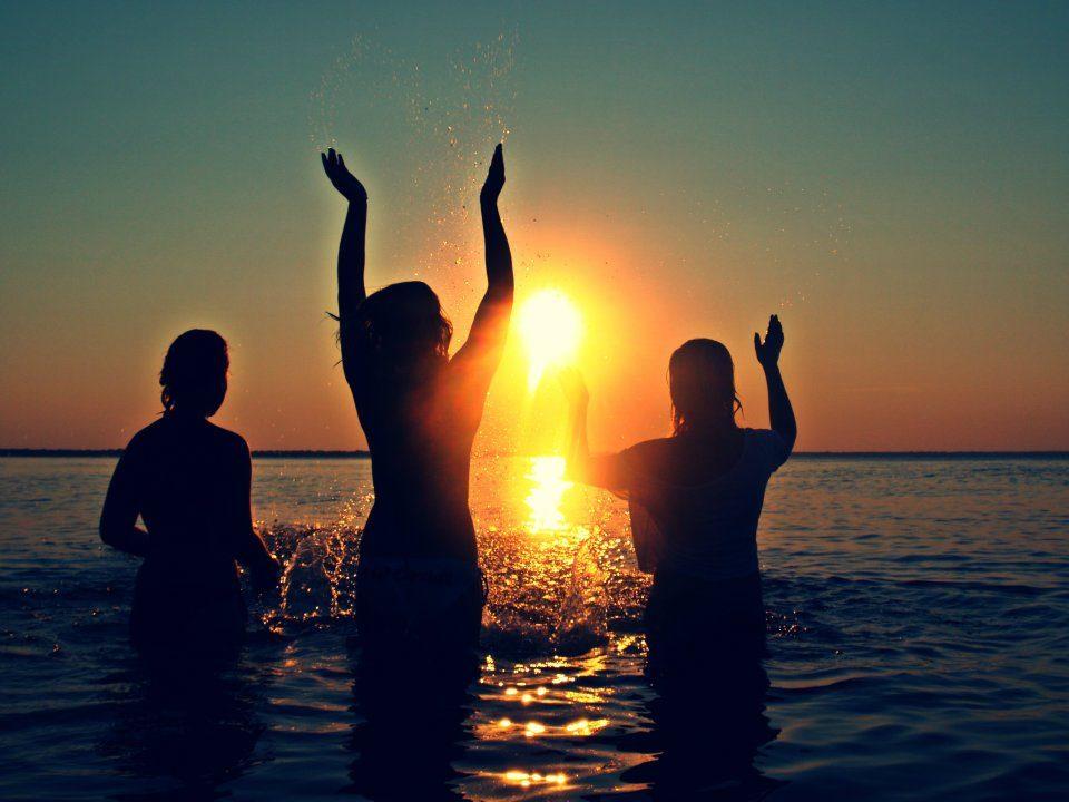 Three friends making a splash at the beach