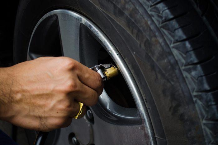 Man filling air into his car tires