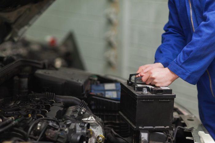 car repair tips - Mechanic checking car battery