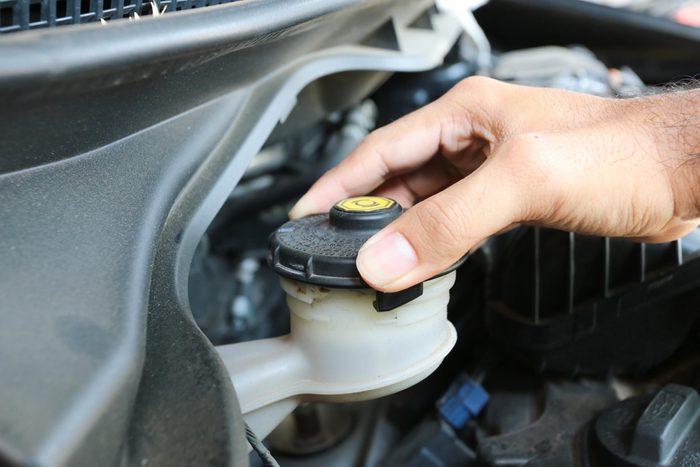 car repair tips - Man checking his brake fluid