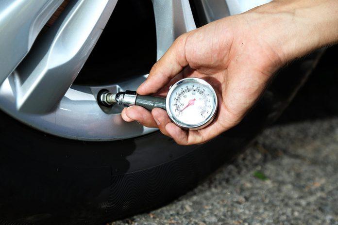 Man checking air pressure of car tire