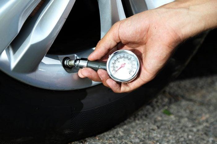 car repair tips - Man checking air pressure of car tire