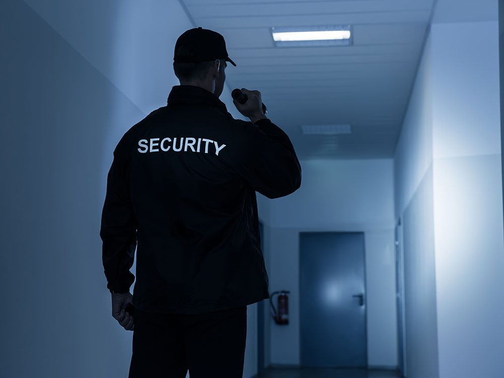 Security guard shining flashlight