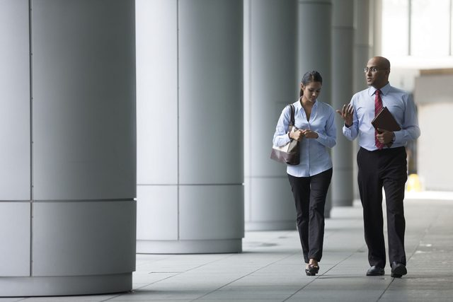 Two colleagues talking and walking