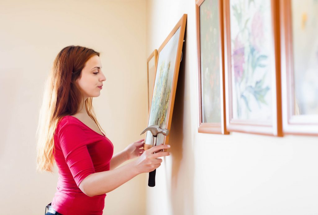 Woman hanging paintings on wall