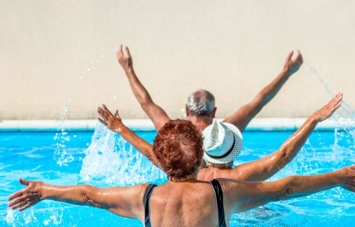 Elderly people exercising in pool