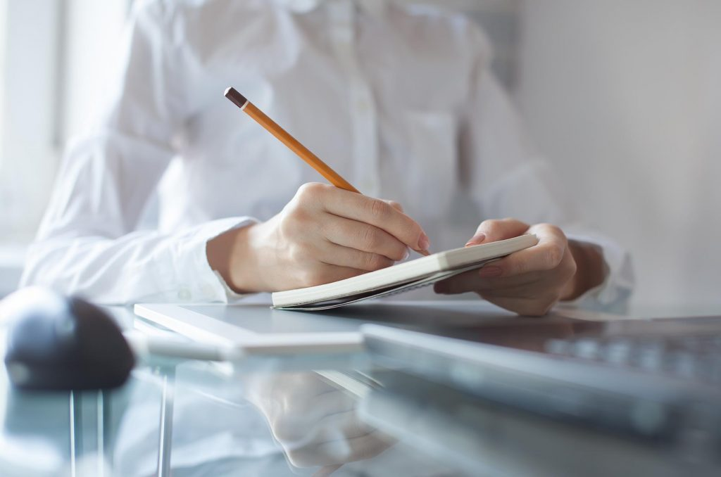 Woman writing in notepad to be more productive