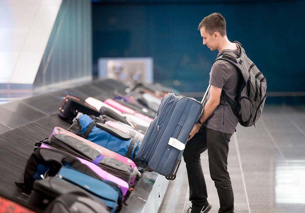 Man at airport luggage carousel