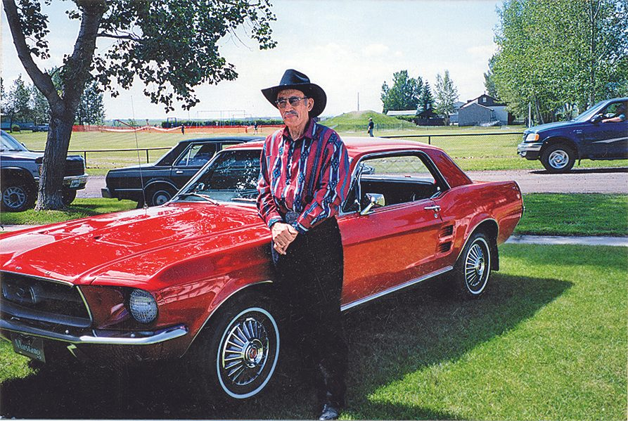 Garth Field standing beside his red Mustang