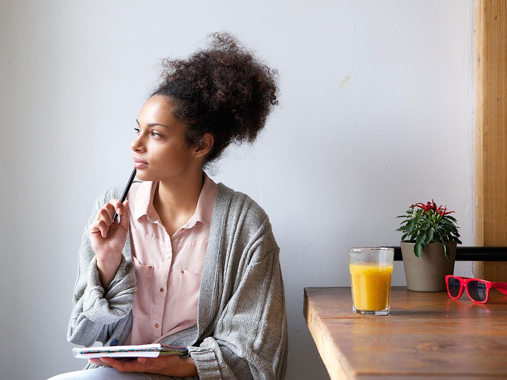 Woman thinking with notepad