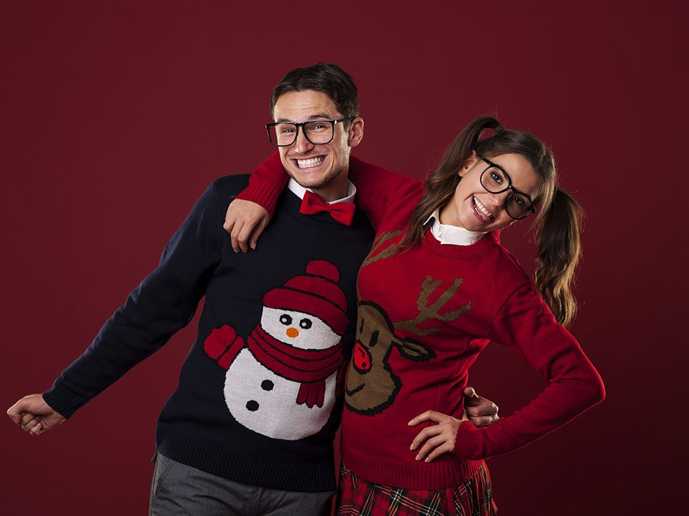 Two friends wearing Christmas sweaters