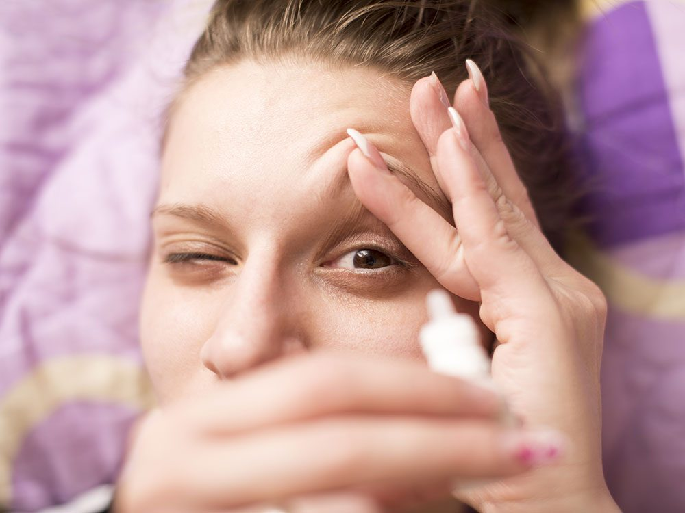 Woman with eye drops