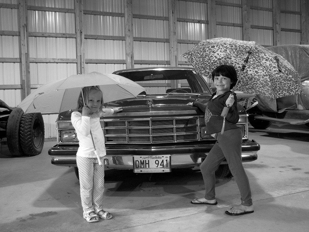 Two kids posing next to car