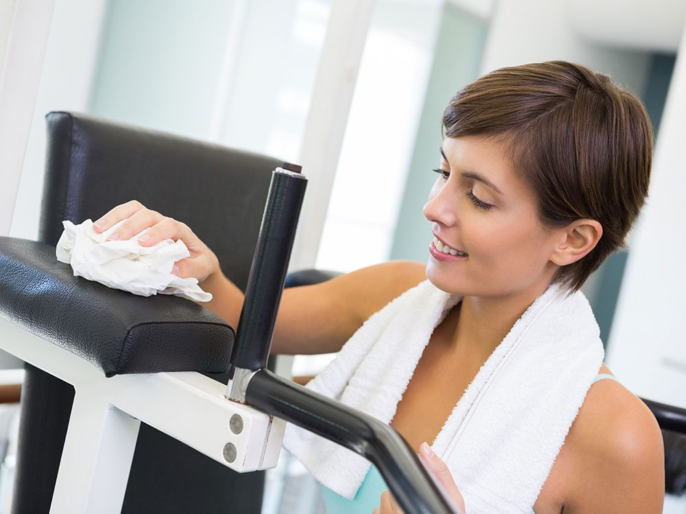 Woman wiping down treadmill