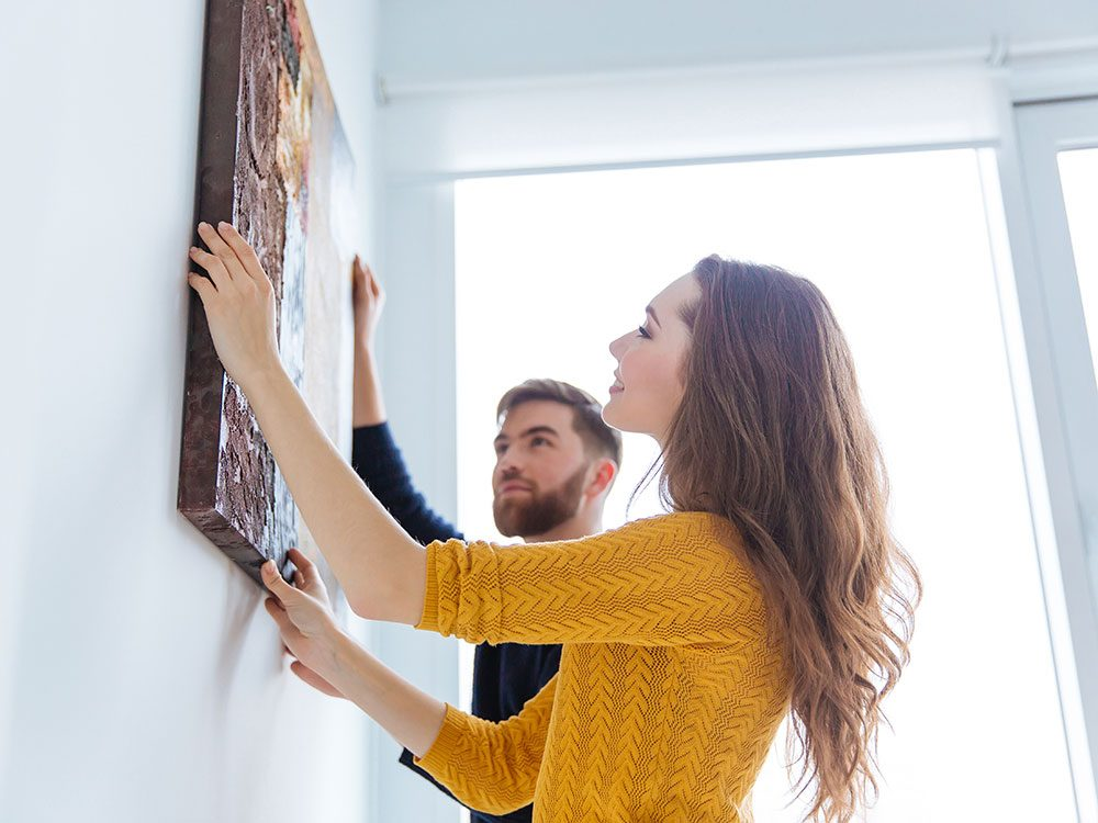 Couple hanging artwork at home