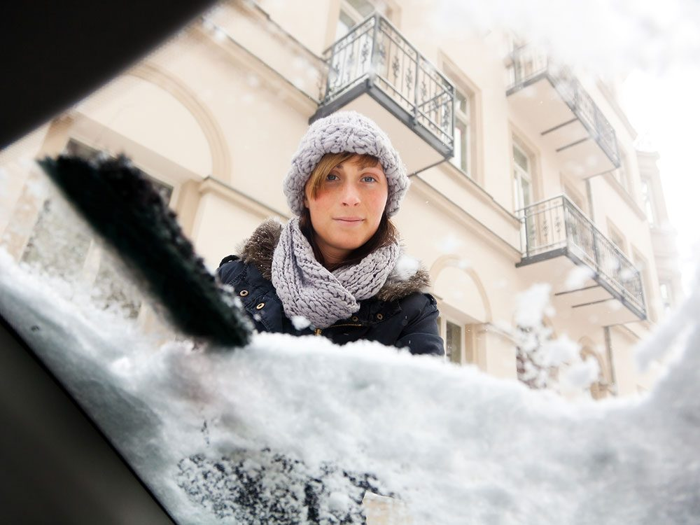 Woman clearing snow off of car windshield