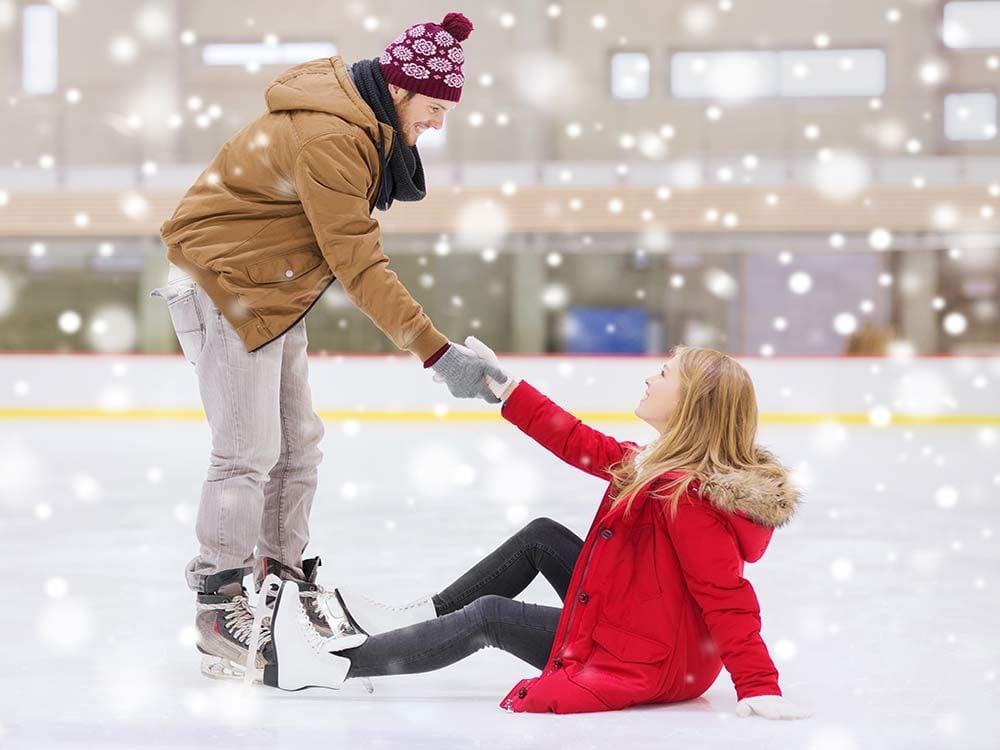 Man helping fallen woman on skating rink