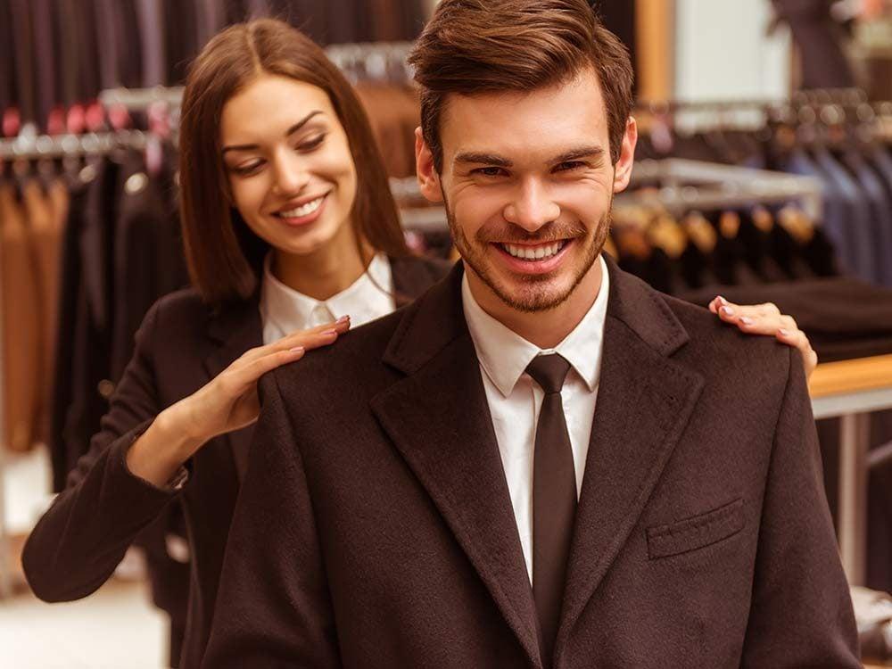 Woman measuring man's suit jacket