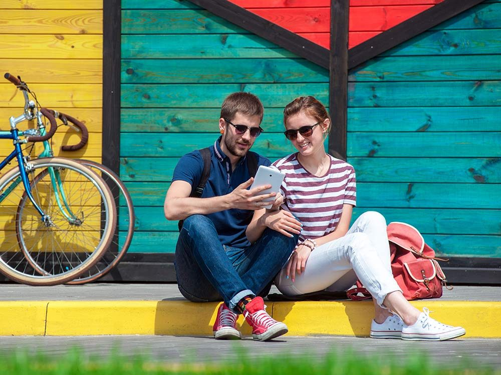Young couple sitting outside on street