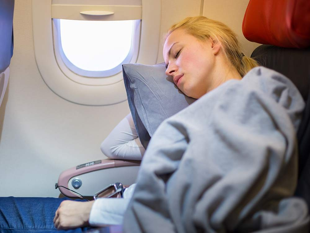 Woman sleeping with blanket during flight