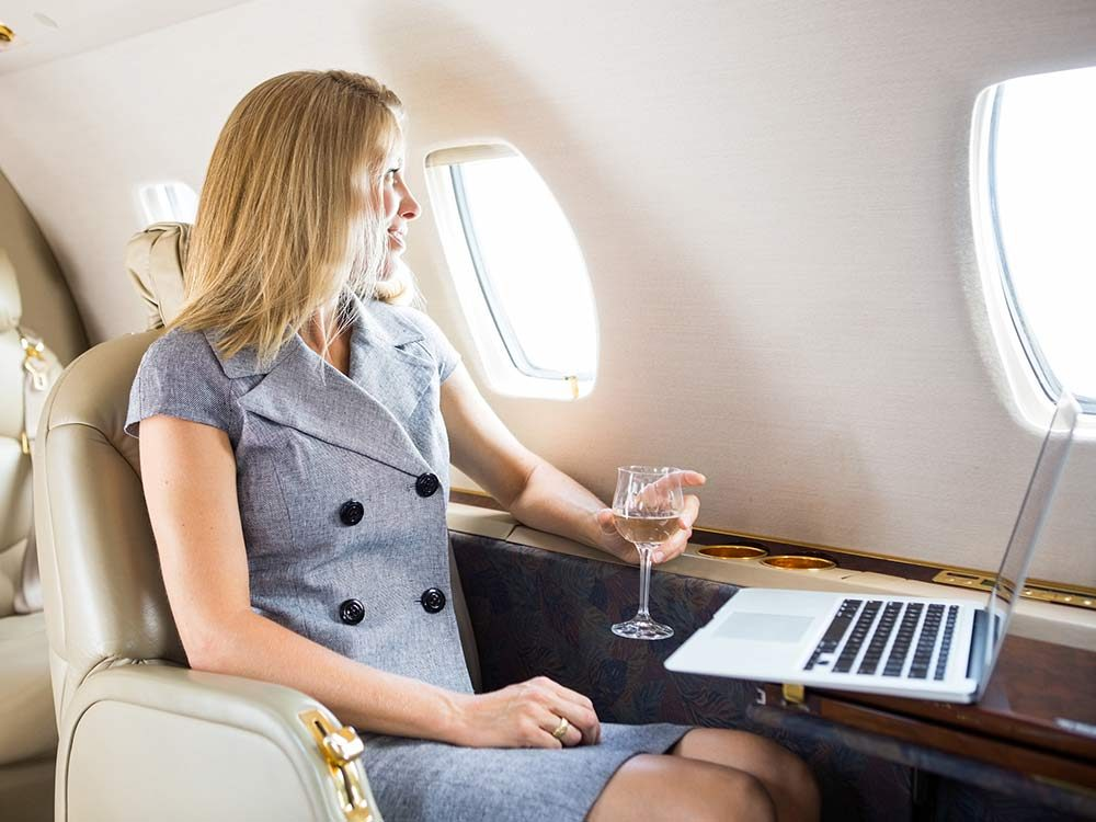Elegant woman drinking wine on an airplane