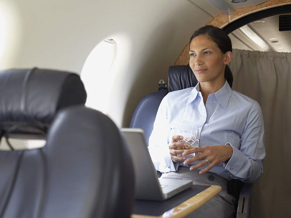 Woman in first class flight drinking