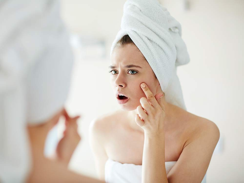 Woman looking at pimple on her face