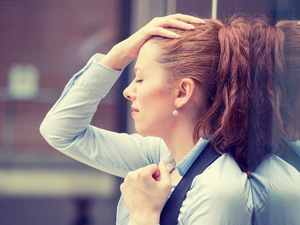 Stressed woman leaning on wall