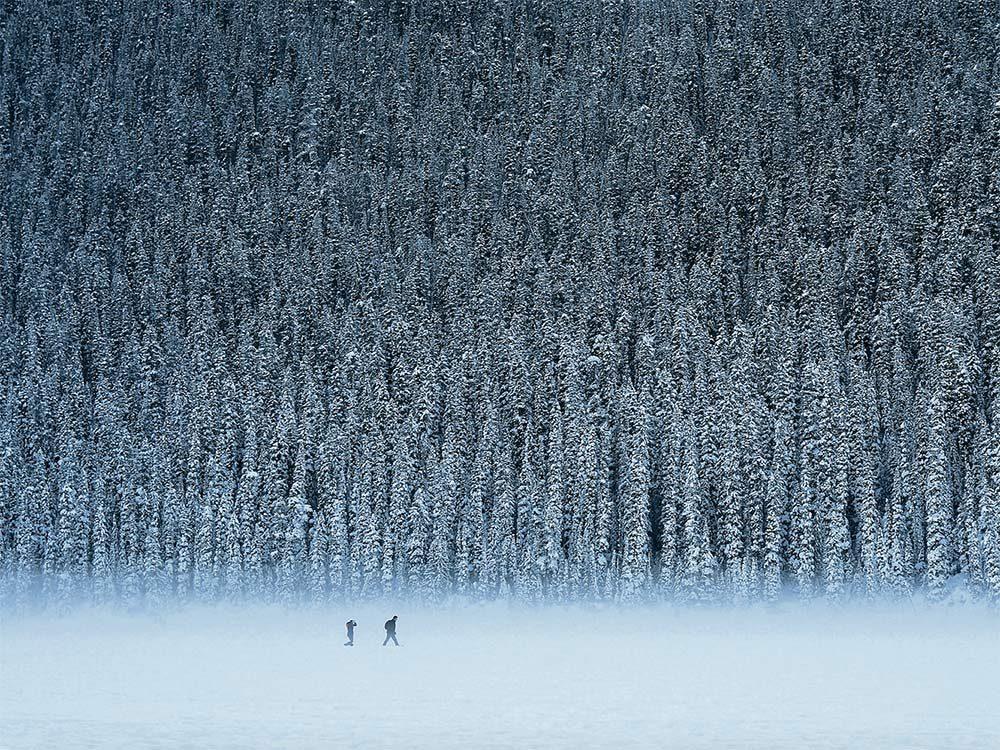 Two people walking in snowy landscape