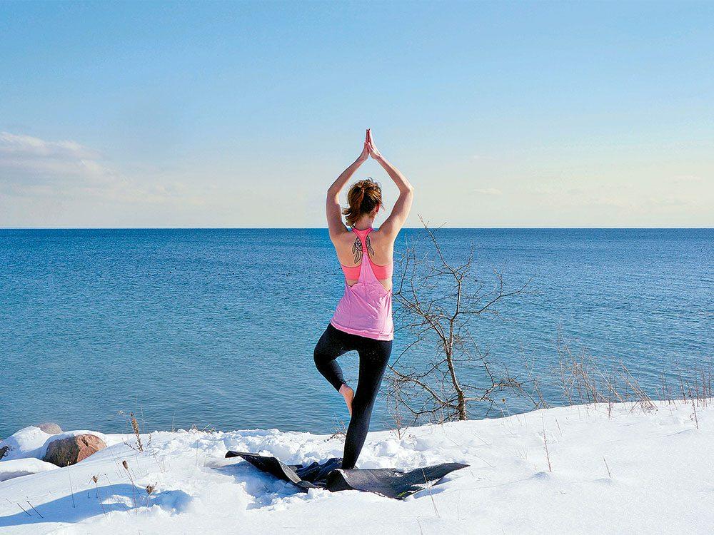 Woman doing yoga on a snowy beach