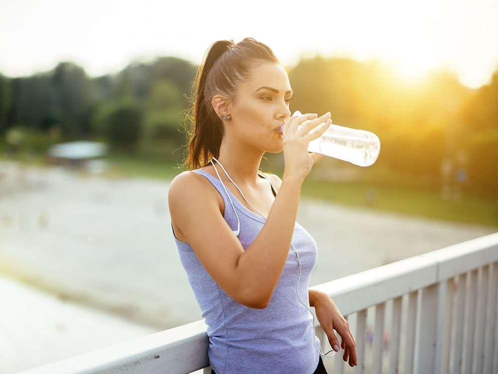 Active woman drinking water