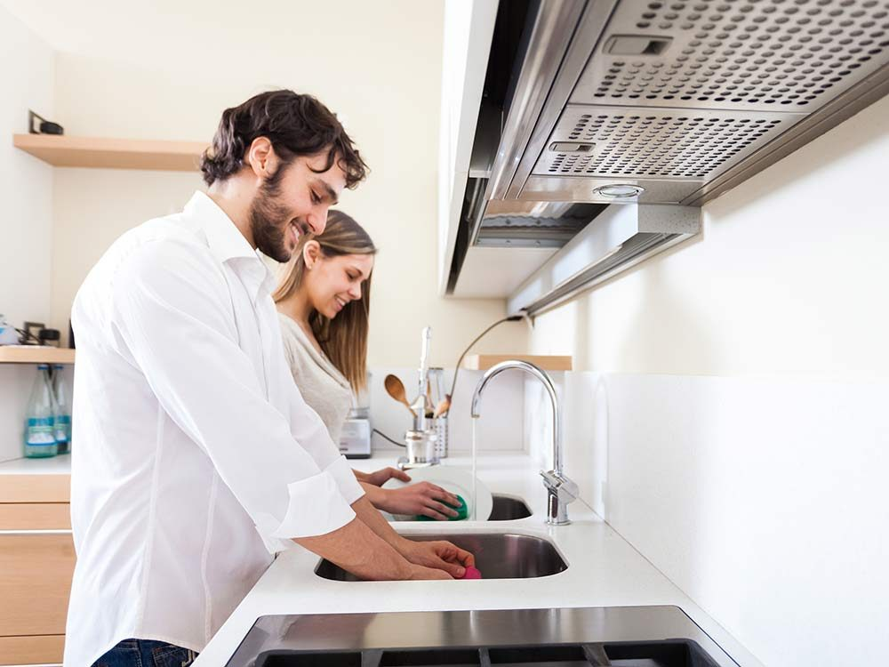 Young happy couple washing dishes