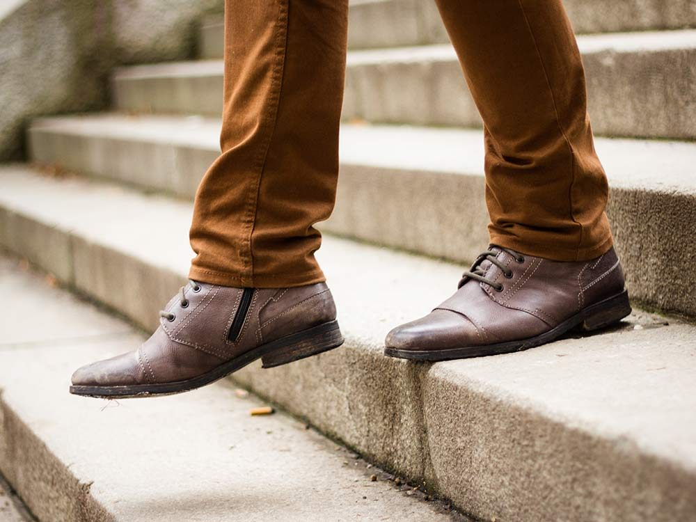 Man in leather shoes walking down stairs