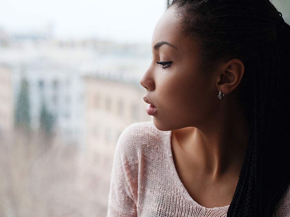 Sad woman looking out of her window
