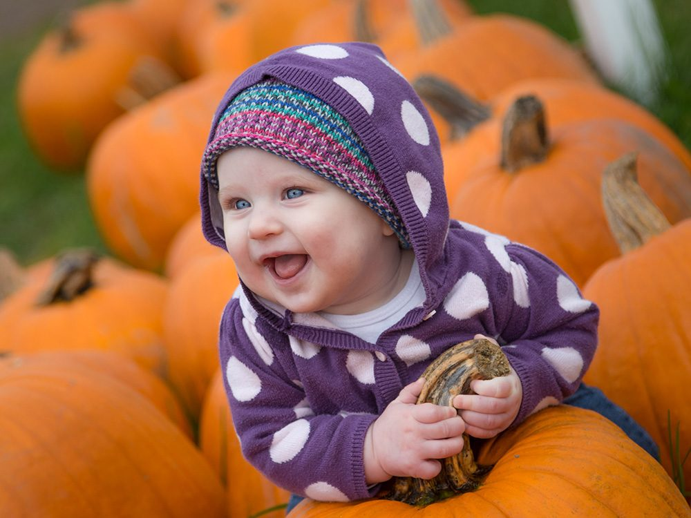 Smiling baby with pumpkins