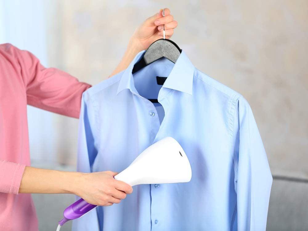 Woman steaming button down shirt