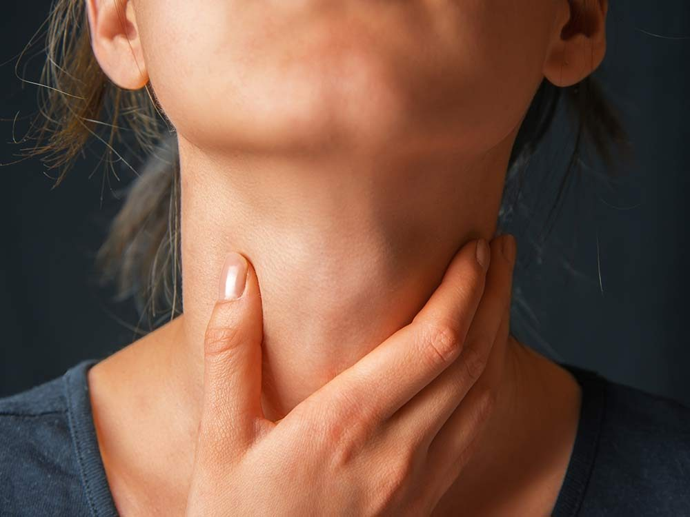Woman holds her sore throat