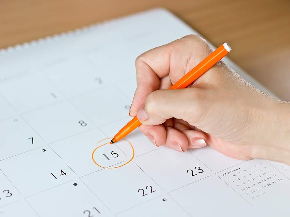 Hand circling date in calendar
