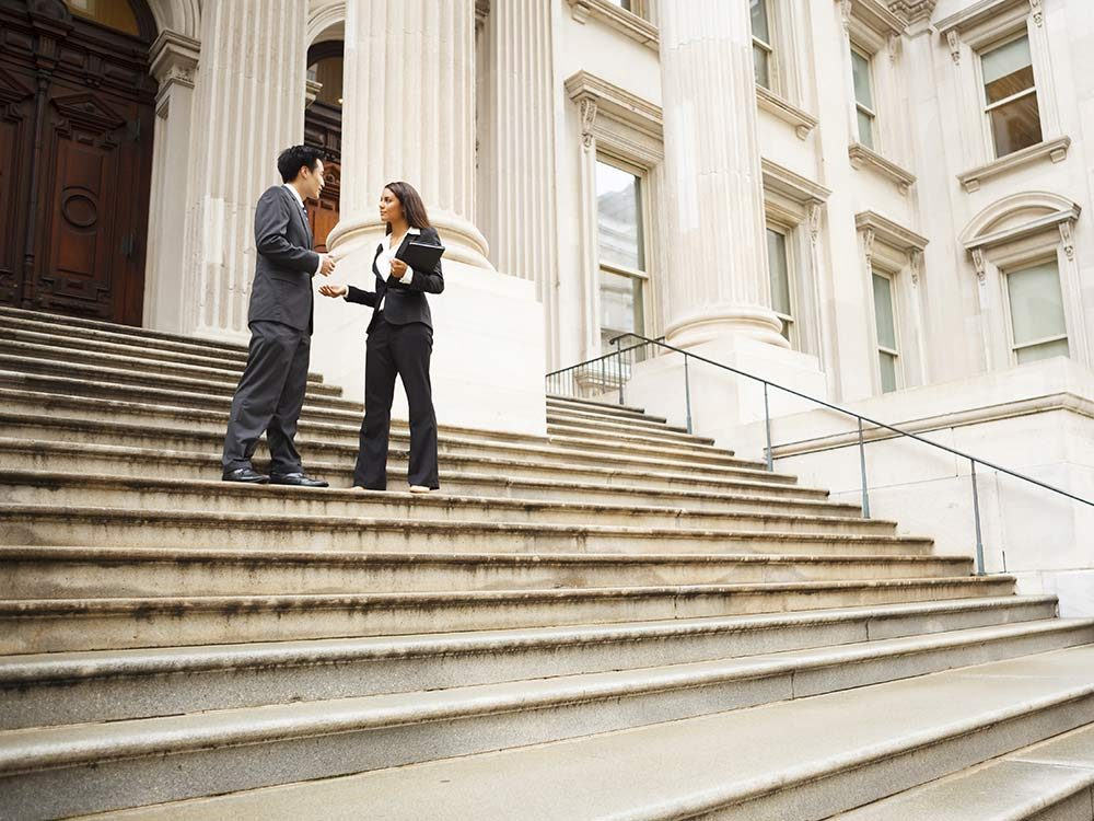 Two lawyers talking on courthouse steps
