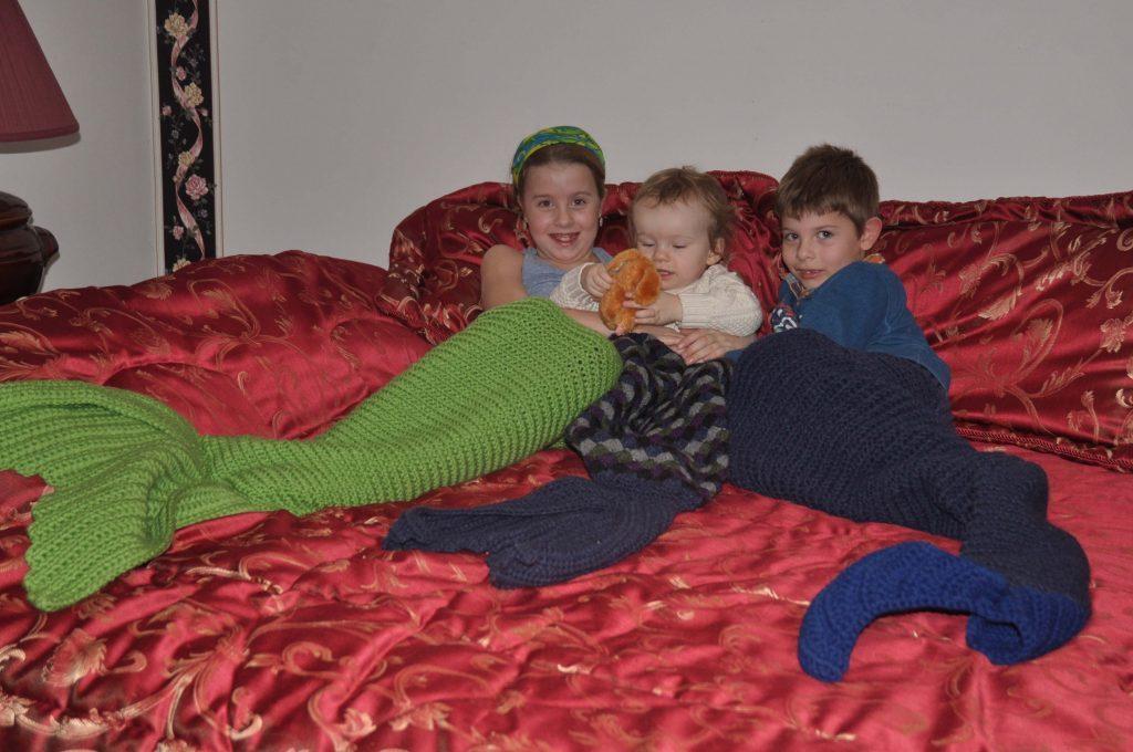 Three children wearing fish blankets