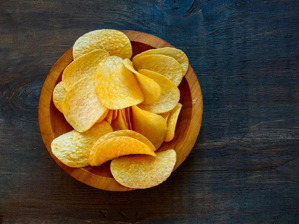 Crispy potato chips in wooden bowl