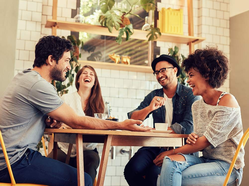Group of friends laughing in a cafe
