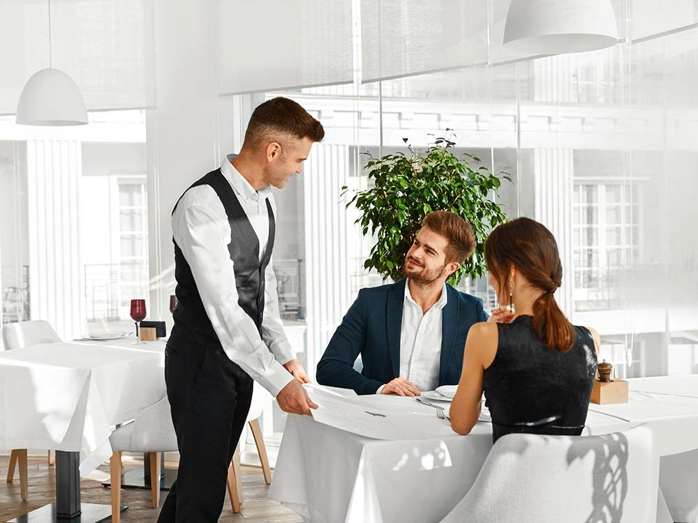 Young couple ordering from waiter in restaurant