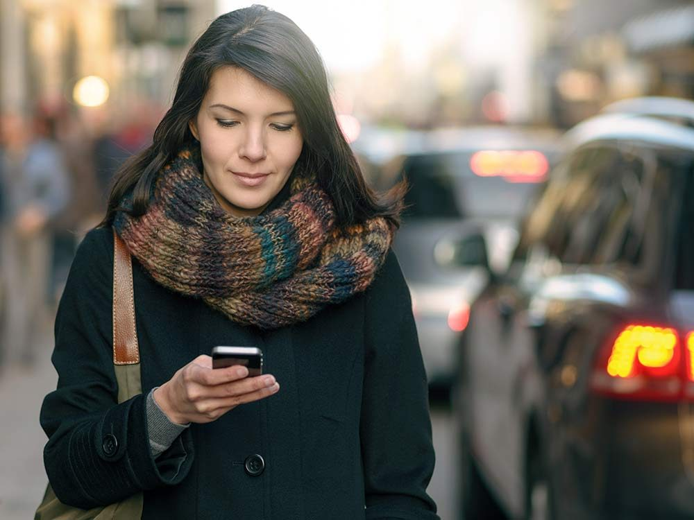 Woman using her phone on busy downtown street