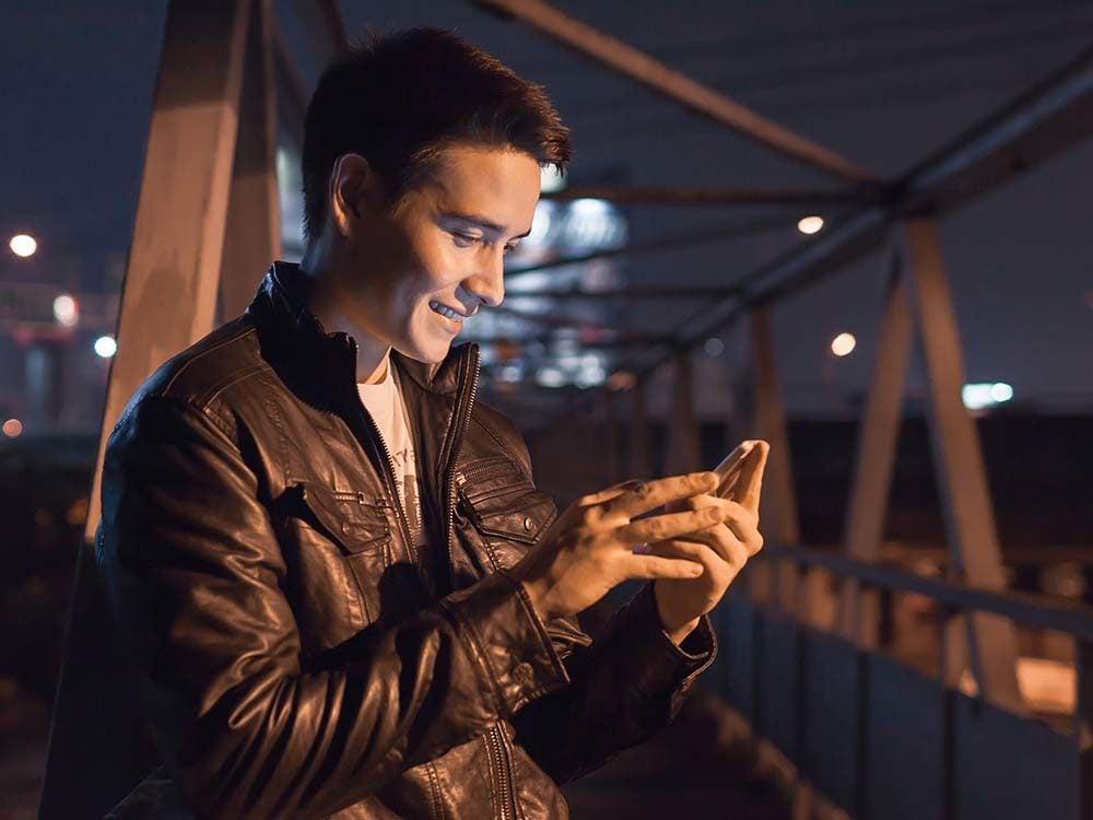 Asian man using smartphone on bridge at night