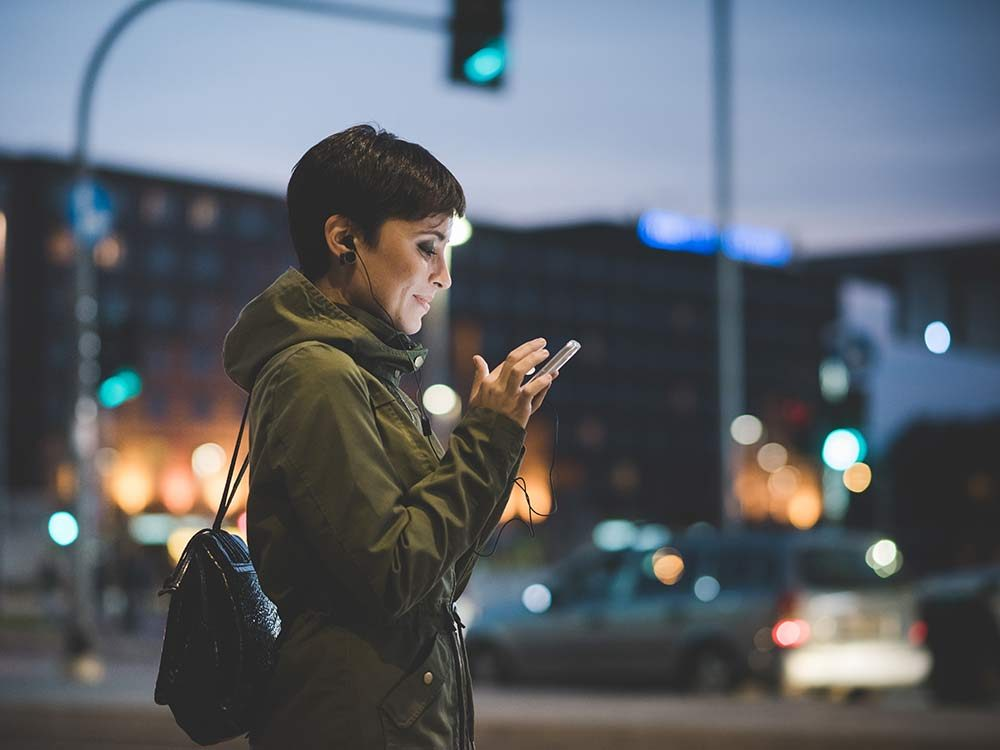Woman on her smartphone outside at night