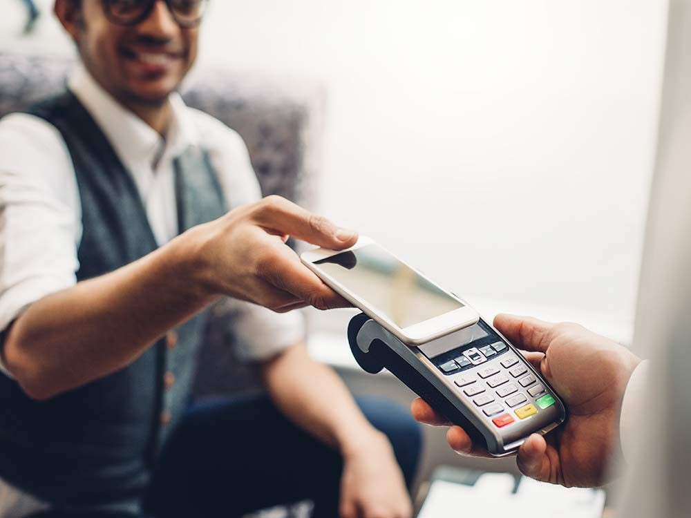 Man using smartphone to pay for product