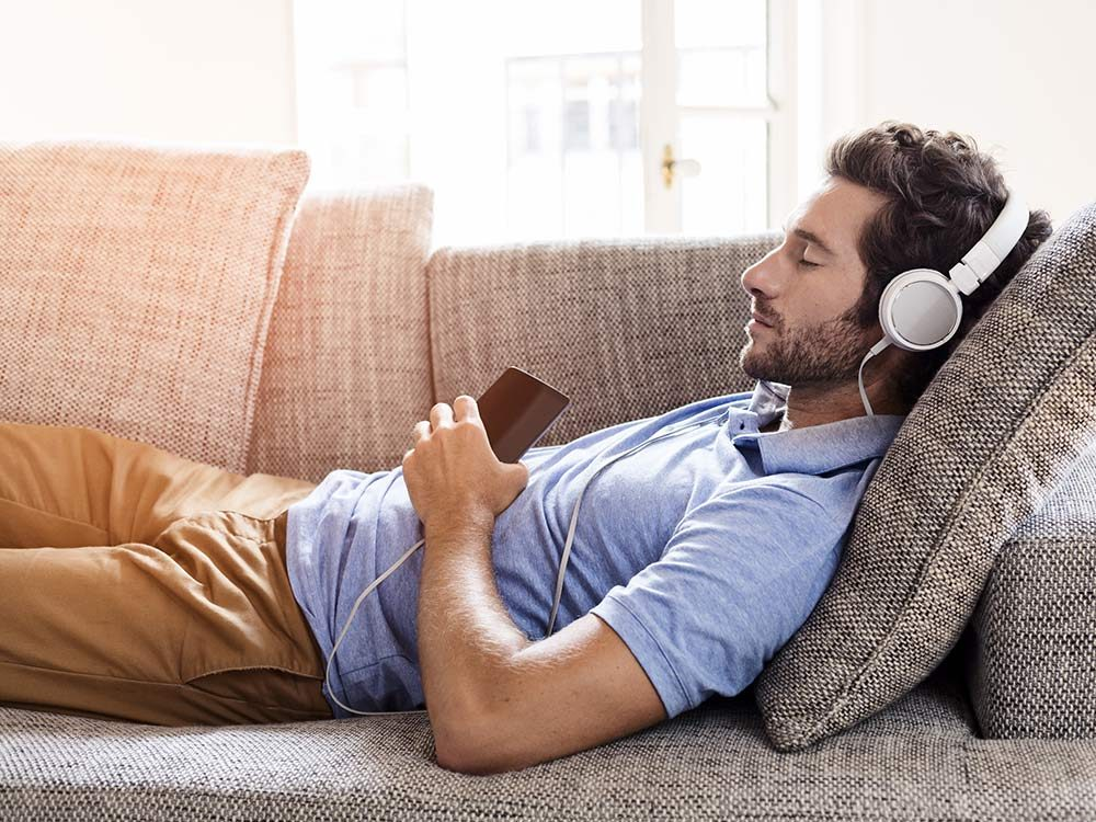 Man listening to headphones will sleeping on couch