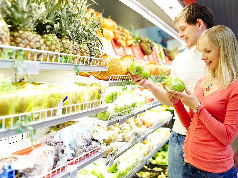 Couple shopping for produce at grocery store